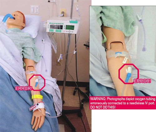 Photo. Oxygen tubing erroneously connected to a needleless IV port on mannequin's forearm.